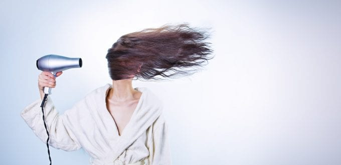 Mujer secándose el pelo